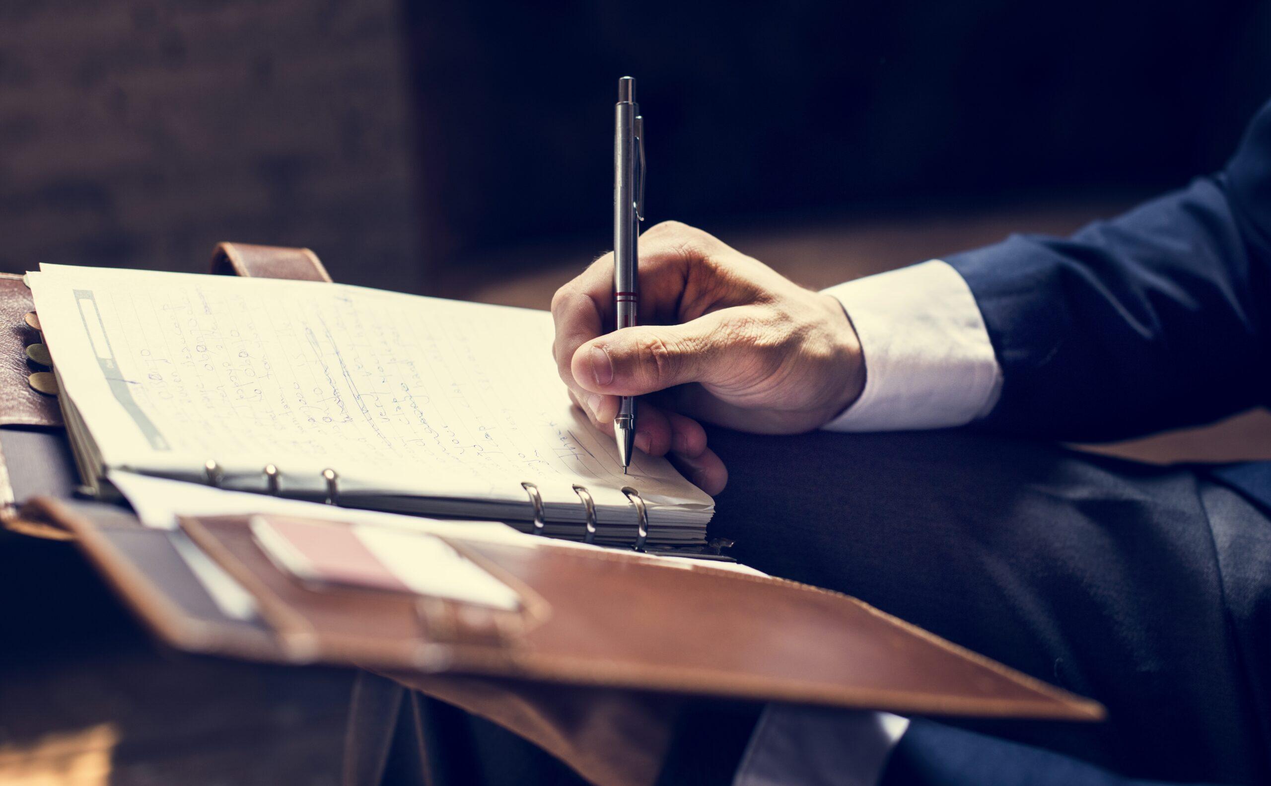 mão com caneta na mão assinando folha