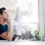 homem pensando olhando através da janela